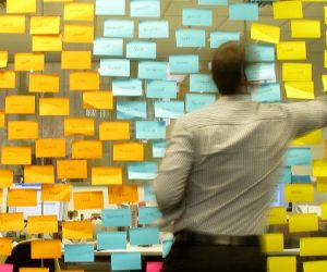 Man arranging multicoloured post-it notes - best apps for students